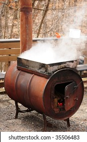 Making maple syrup - steam rising off a vat of sap being boiled on an outdoor stove