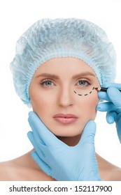 Making marks on face. Portrait of beautiful young woman in medical headwear looking at camera while doctors hands in gloves making marks on her face isolated on white