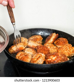 Making meatballs in black iron fry pan on hotplate hub with fork
