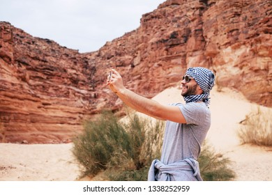 Making memories. Pleasant man wearing grey outfit ,in front of rocks, sand, blue sky and green bushes is making a photo of beauty around him with smartphone