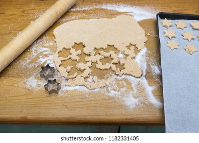 Making a mess of baking star shaped Christmas cookies - with rolling pin, biscuit cutter, dough, and baking sheet with paper on wooden kitchen bench top