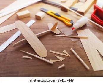 Making model airplane from wood. Wooden air plane handcrafted with balsa wood, on work table by the window. Airplane, cutter knife, balsa wood material and glue on table.