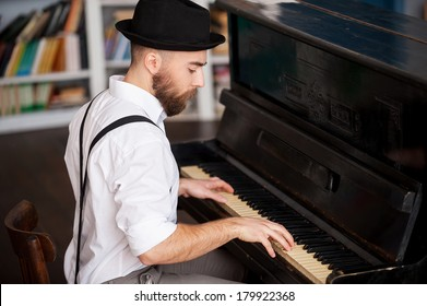 Making music. Profile of a handsome young bearded men playing piano
