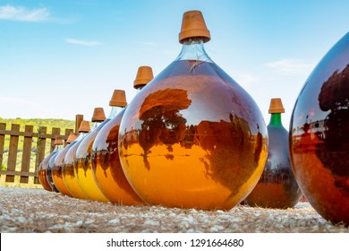 Making of natural sweet dessert muscat liqueur white wine outside in big round glass antique demijohn bottles in Frontignan, France