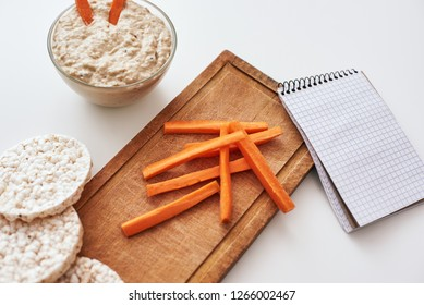 Making a new delicious recipe from hummus with carrot sticks.