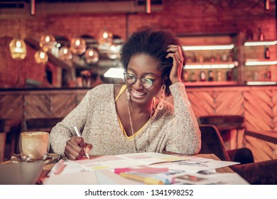 Making notes in notebook. African-american beautiful young adult smiling lady in glasses making notes in notebook spending time in tea-house