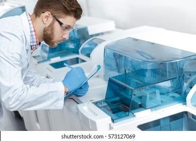 Making notes. Professional male scientist making notes on his clipboard watching analyzing machine during his research at the modern laboratory professionalism experiment science medicine concept