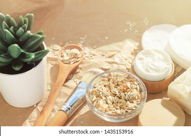 Making nourishing homemade mask with oatmeal and fresh yogurt cream. Cosmetic Jars on sunlit table in the morning, facial cleansing ingredients on craft paper background.