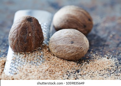 Making nutmeg powder process. Nuts silver grater. Kitchen still life photo. Shallow depth of field, aged brown rusty background. Selective focus.