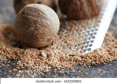 Making nutmeg powder process. Nuts silver grater. Kitchen still life photo. Shallow depth of field, aged brown rusty background. Selective focus
