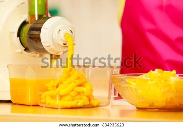 Making orange juice nutritious vitamin packed drink in juicer machine at home in kitchen. Healthy eating, vegetarian food, dieting concept