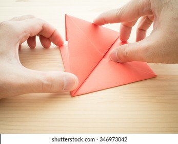 Making origami paper with hands.