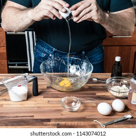 Making paleo style pancakes with coconut flour and honey by cracking eggs into the bowel.
