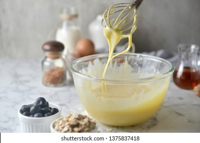 Making pancakes, cake, baking side view of baker hands pouring batter and whisking batter in bowl. Concept of Cooking ingredients and method on white marble background, Dessert recipes and homemade.