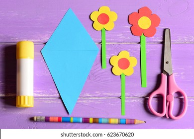 Making paper crafts for mother's day or birthday. Step. Paper flowers, scissors, glue stick, flowers templates, pencil on a table. Set for kids art activity at home or in kindergarten. Top view