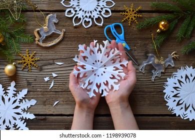 Making paper snowflakes with your own hands. Children's DIY. Merry Christmas and New Year concept.