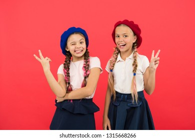Making peace signs. French style girls. Little kids wearing stylish french berets. Cute girls having the same hairstyle. Small children with long hair plaits. Fashion girls with tied hair into braids.