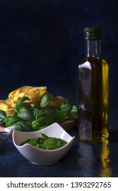 Making pesto. The table with ingredients to produce basil pesto. Mortar, fresh basil herbs, pine nuts, olive oil, parmesan cheese, garlic, bowl with pesto, grater, fresh homemade pasta.