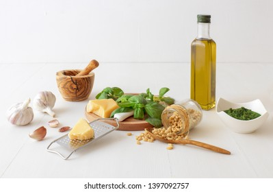 Making pesto. The table with ingredients to produce basil pesto. Mortar, fresh basil herbs, pine nuts, olive oil, parmesan cheese, garlic, bowl with pesto, grater, fresh homemade pasta. White backgr.