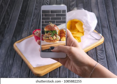 Making photo with phone of bacon burger with nachos on wooden plate. Food blogging.