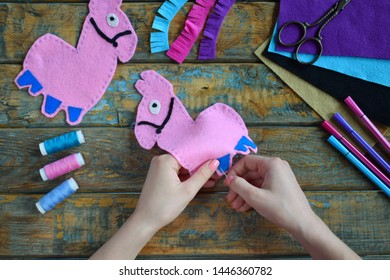 Making pink lama. Sewing toys from felt with your own hands. DIY concept for children. Handmade crafts. Step 3. Sew all details of toy.