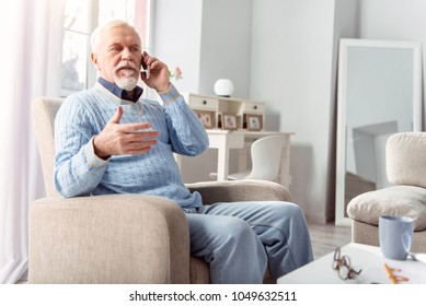 Making plans. Pleasant elderly man sitting in the armchair in the living room and talking on the phone with his friend, discussing their dinner arrangement