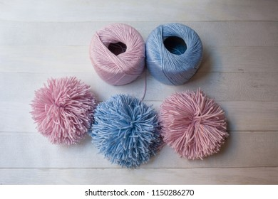 Making of pom-pom, how to make pom-poms, do it yourself, diy, blue and pink handmade cotton pom-poms, hobby crafts, wooden background