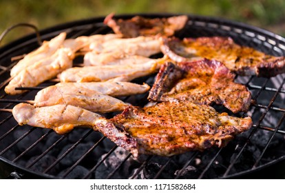 Making pork chops and chicken skewers on barbecue grill. Preparing meat and grilling on direct heat in nature at back yard BBQ picnic.