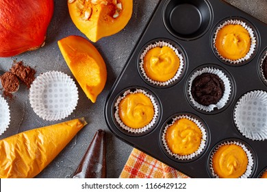 making pumpkin chocolate muffins for halloween party. ingredients at the background, view from above, close-up