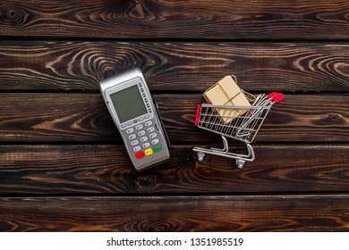 making purchase online with card machine and mini trolley on office desk background top view