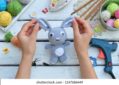 Making rabbit with carrot. Crochet bunny for child. On table threads, needles, hook, cotton yarn. Handmade crafts. DIY concept. Small business. Income from hobby.
