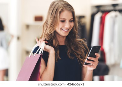 Making the retail connection. Beautiful young woman with shopping bags using her smart phone with smile while standing at the store