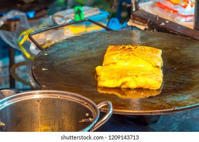 Making Roti which is Thai style pancakes in open street night market in thailand. Roti with Banana and eggs for a tasty dessert. Roti crepes on the hot oily stove.