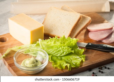 making sandwich with bread, cheese, salad and ham with hands on wooden cutting board