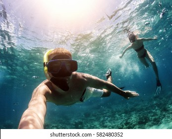Making selfie underwater with action camera. Couple snorkeling in deep blue sea.