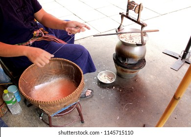 making silk with silkworm cocoons by handmade.boiling yellow white silkworm cocoons to make silk thread. colorful silknest to made silk dyeing by hand.