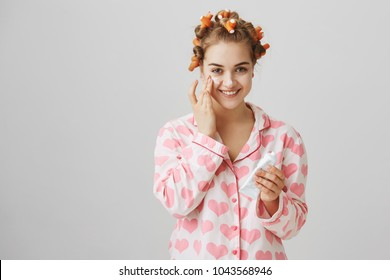 Making skin beautiful. Indoor shot of cute slender female in hair curlers and pyjamas holding facial cream and wiping it on face, smiling broadly while standing over gray background.