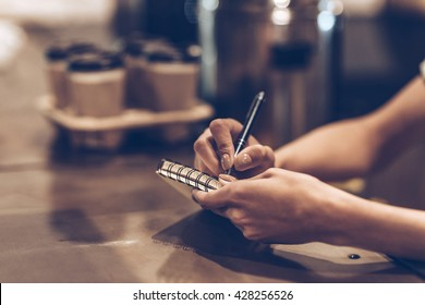 Making some notes. Part of close-up of young woman writing in notebook while standing at bar counter