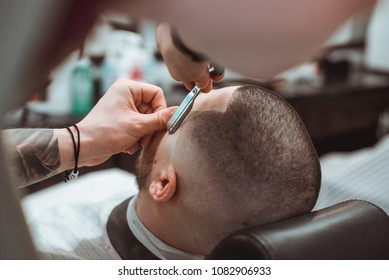 Making stylish curly haircut at salon closeup. Man sitting with closed eyes while barber shaving him with razor. Beauty, modern style, lifestyle, trend concept