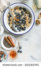 Making of super seedy vegan baked oatmeal with blueberries and walnuts. Power breakfast for healthy, super food and clean eatind concept. Overhead view