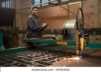 Making sure equipment works well. Professional industrial worker controlling plasma cutting machine operation writing on his clipboard at the metalworking workshop