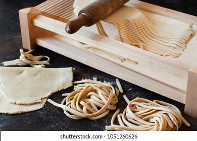 Making tagliolini pasta alla chitarra with a tool close up