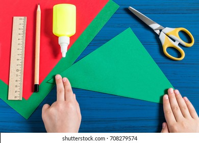 Making three-dimensional Christmas tree from paper to decorate room. Original children's art project. DIY concept. Step-by-step photo instructions. Step 2. Child makes triangle out of square