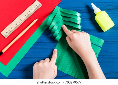 Making three-dimensional Christmas tree from paper to decorate room. Original children's art project. DIY concept. Step-by-step photo instructions. Step 6. Child glues together strips