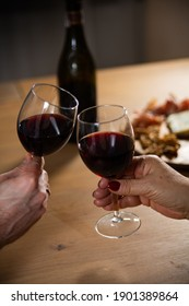 Making a toast by clinking two glasses with red wine. Wine tasting with cheese board. Celebrating special occasions with friends, family