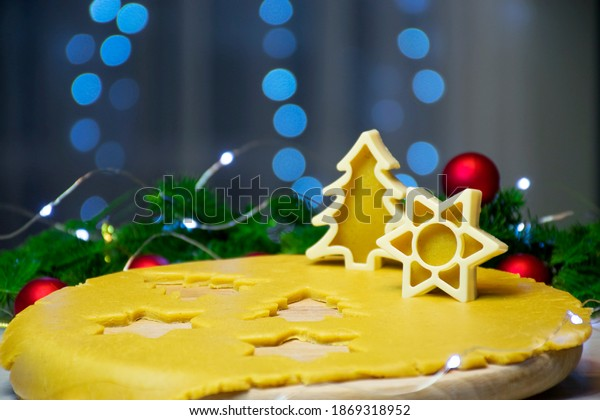 Making tradition Christmas gingerbread cookies. Raw dough with cutters Christmas tree and star shape holidays decor, lihjts and bokeh on background. New Year card, winter holidays entertainment
