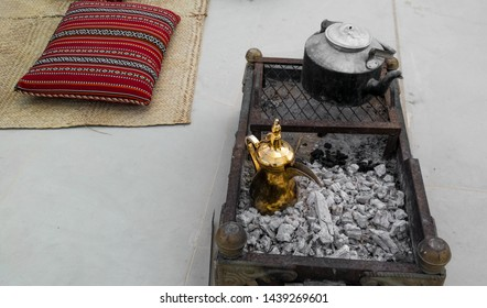 Making traditional Arabian coffee - golden Arabic and Middle Eastern coffee pot (Dallah) on top of charcoal around Arabic decorations