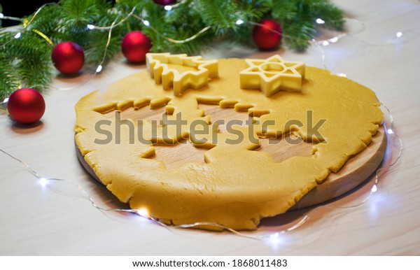Making traditional Christmas gingerbread and honey cookies. Raw dough with cutters of Christmas tree and star shape, fir branches and toys on background. Homemade bakery, winter holidays entertainment