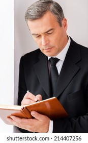 Making urgent notes. Confident mature man in formalwear writing something in note pad while leaning at the wall