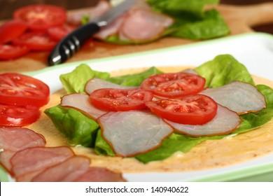 Making wrap tortilla sandwich with ham, tomato, lettuce.